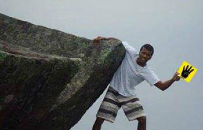 نشطاء يتداولون صورة مزيفة لشخص يتدلى من أعلى جبل يحمل شعار رابعة