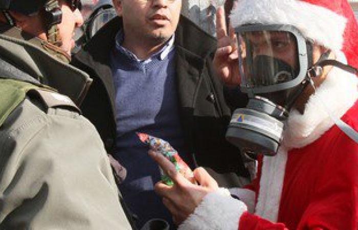 بالصور.. فلسطينيون بملابس بابا نويل يشتبكون مع الجيش الاسرائيلى فى الضفة الغربية