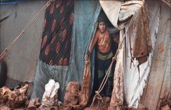 هربا من البرد.. سكان مخيمات إدلب يشعلون النار في أغراضهم