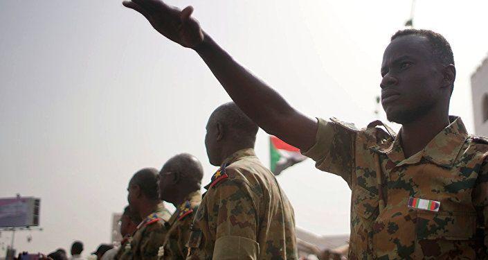 جنود في السودان بالقرب من متظاهرين أثناء مظاهرة تطالب بتنحي عمر البشير