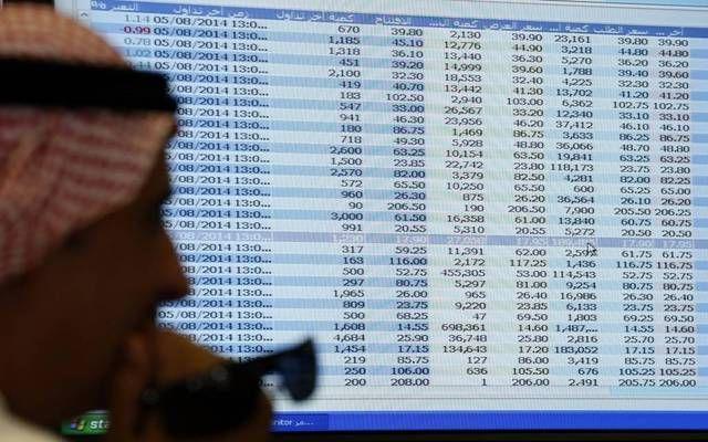 متداول أمام شاشة تعرض الأسهم السعودية