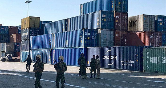 جنود يرافقون مسؤولين حكوميين يقومون بجولة في محطة الحاويات في ميناء عدن