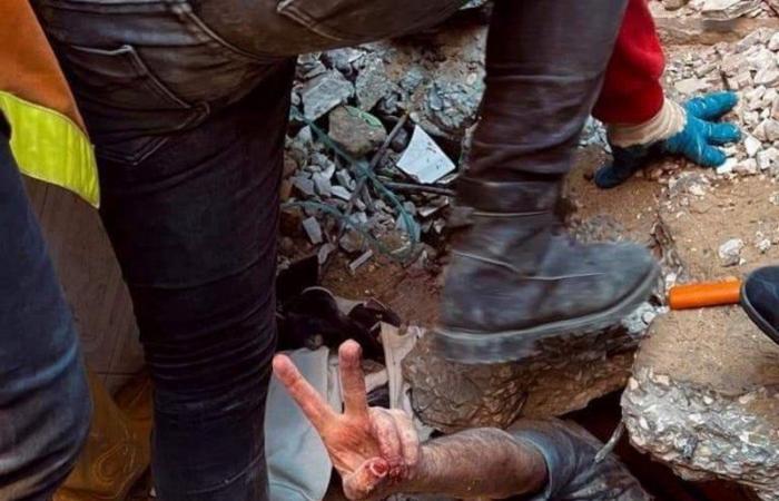 صورة الصمود.. شاب فلسطيني يلوح بعلامة النصر أثناء انتشاله حياً من تحت ركام منزله