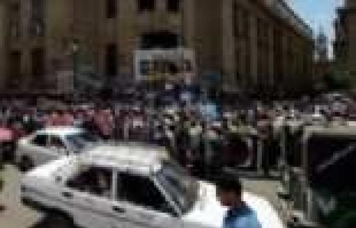 مجندو الأمن المركزي يلوحون بإشارات خارجة للمتظاهرين من شرفات دار القضاء