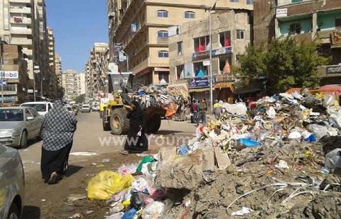 بالصور.. تلال القمامة تعيق حركة المرور بميدان الساعة شرق الإسكندرية